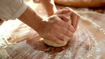 stock-footage-baker-hands-kneading-dough-in-flour-on-table-slow-motion